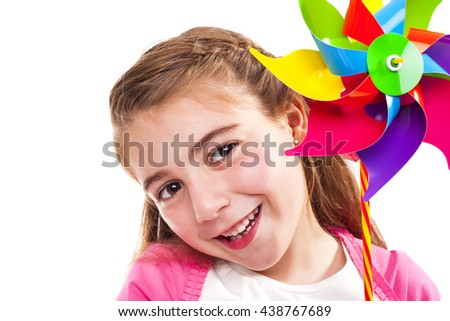 Happy smiling little girl holding a colorful toy windmill, isolated on white background - stock photo