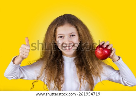 Happy, smiling little girl holding an red apple, and thumb up isolated on yellow background.Healthy food,Healthy Thinking,Positive thinking.Idea. - stock photo