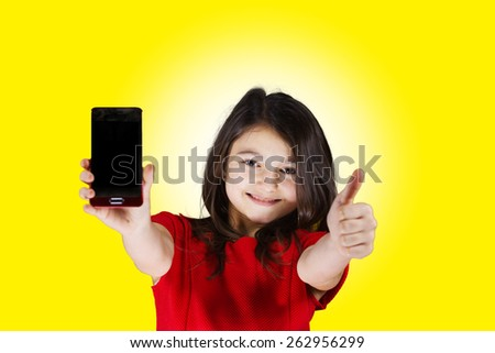 Happy Smiling Little Girl holding mobile phone and gesturing making thumb up while standing isolated on white.Success,Communications, - stock photo