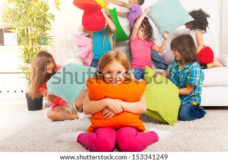Happy smiling little girl hugging pillow with large group of her friends pillow fighting on the background