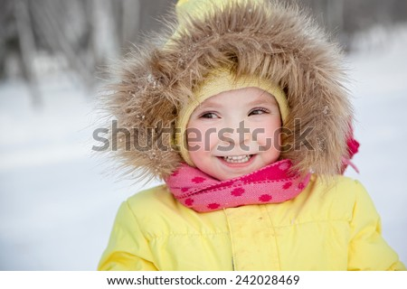 Happy smiling little girl in winter clothes - stock photo