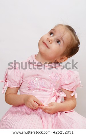 Happy smiling little girl is looking at the left side and up. Cheerful kid. - stock photo