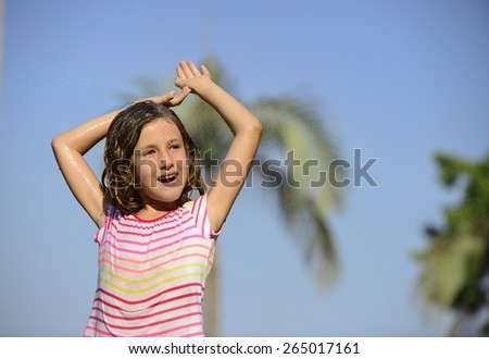 Happy smiling little girl outdoor in a sunny day enjoying the light rain. - stock photo