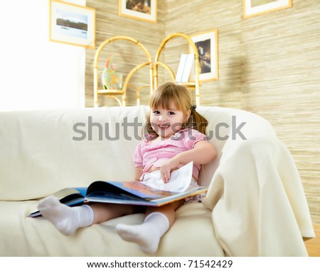 happy smiling little girl sitting on the sofa and reading a book - stock photo