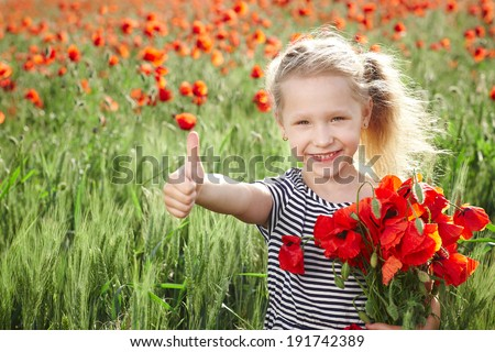 Happy smiling little girl standing on the poppy meadow, holding a posy, showing thumb up gesture - stock photo
