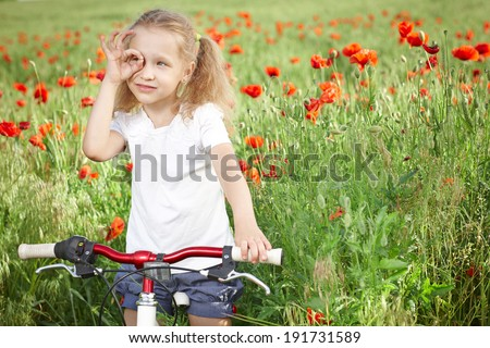 Happy smiling little girl standing with bicycle on the poppy meadow looking away through circled fingers - stock photo