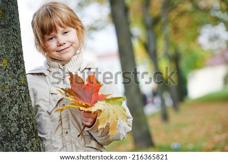 Happy smiling little girl with fallen leaves in autumn park - stock photo