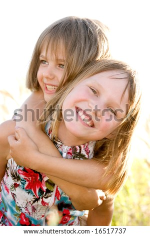 Happy smiling little sisters on green summer meadow background