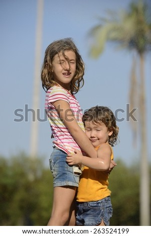 Happy smiling little sisters outdoor in a sunny day enjoying the light rain. - stock photo