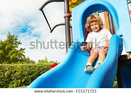 Happy smiling little three years old boy about to slide on blue playground - stock photo