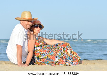 happy smiling & looking at camera mature couple sitting at seashore on sandy beach back to back on the summer outdoors background - stock photo