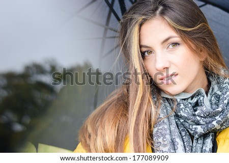 happy smiling & looking at camera young woman with umbrella wearing warm yellow coat outdoors - stock photo