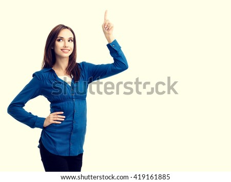 Happy smiling looking up young woman in casual smart blue clothing, showing something or copyspace for text or slogan - stock photo
