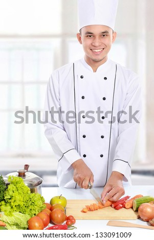 happy smiling male chef cutting fresh carrot - stock photo