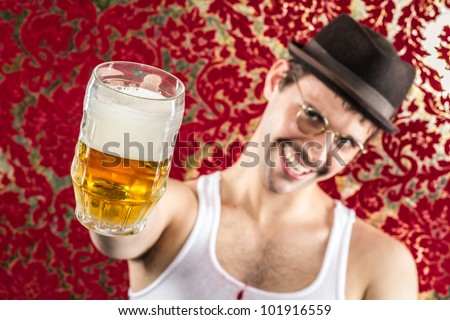 Happy smiling man at pretty retro bar toasting with frothy mug of golden beer in brown vintage hat, glasses, and mustache, wearing white tank top