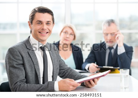 Happy smiling man having an interview or business meeting with employers. Office interior with big window - stock photo