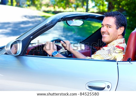 Happy smiling man in a convertible car. Driver. - stock photo