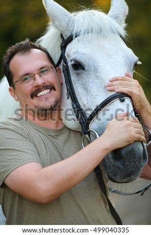 Happy smiling man in glasses hugs beautiful white horse head in park