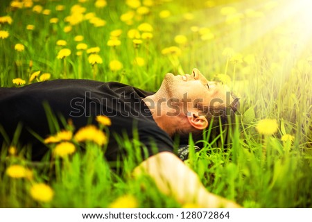 Happy smiling man lying on grass with yellow dandelion at sunny day