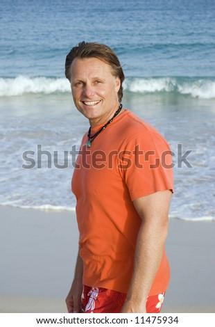 Happy smiling man on beach. - stock photo