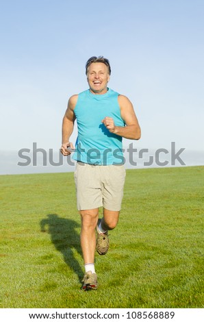 happy smiling man running in a park wearing a blue tank top and grey shorts.