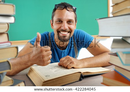 Happy smiling man showing thumbs up gesture in surrounded by books. Photo adult teacher in classroom, creative concept with Back to school theme - stock photo