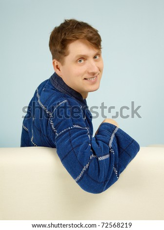 Happy smiling man sitting on a couch in his dressing gown on blue