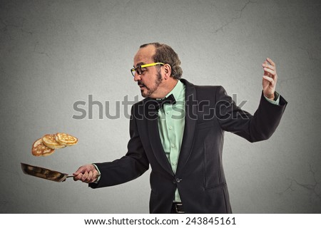 Happy smiling man tossing pancakes on frying pan isolated on grey wall background. Positive face expression emotion, Kitchen fun concept   - stock photo