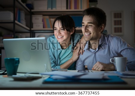 Happy smiling married couple at home using a laptop, connecting to internet and networking, communication and internet concept - stock photo