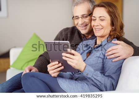 Happy smiling married couple sharing a tablet computer to surf the internet as they sit arm on arm on a sofa at home
