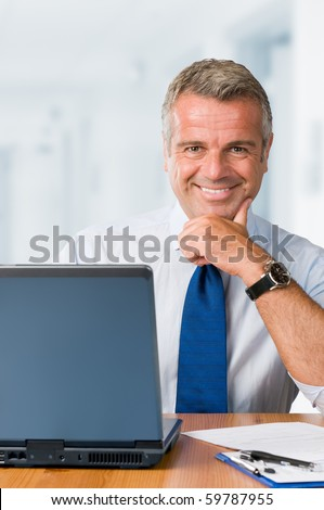 Happy smiling mature businessman looking at camera and working in his modern office - stock photo
