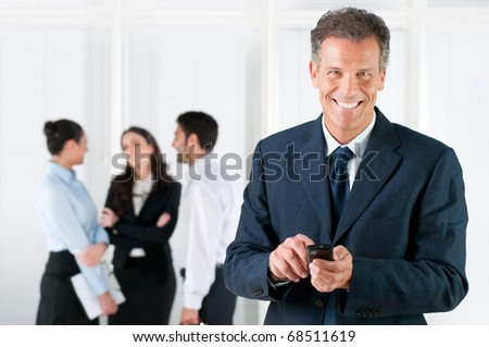 Happy smiling mature businessman receiving positive news on his smart phone at office - stock photo