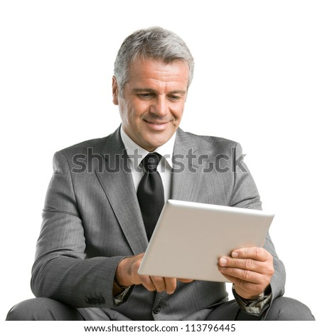 Happy smiling mature businessman surfing the net and working with digital tablet isolated on white background