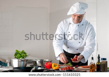 Happy smiling mature chef preparing a meal with various vegetables - stock photo