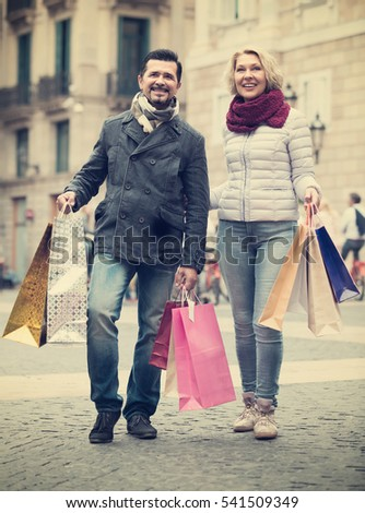 Happy smiling mature couple holding shopping bags walking by street