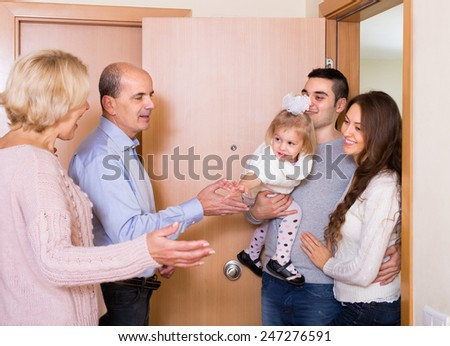 Happy smiling mature couple meeting kids and grand children at doorstep. Focus on girl  - stock photo