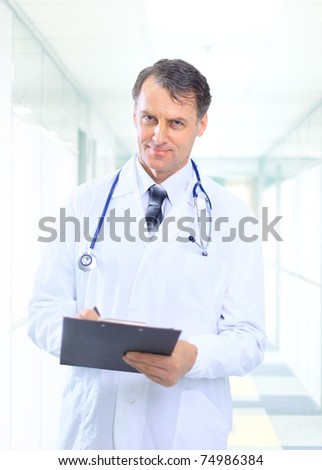 Happy smiling mature doctor writing on clipboard in a modern hospital