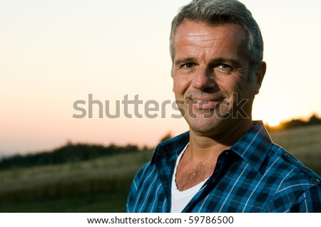 Happy smiling mature man looking at camera outdoor in a meadow - stock photo