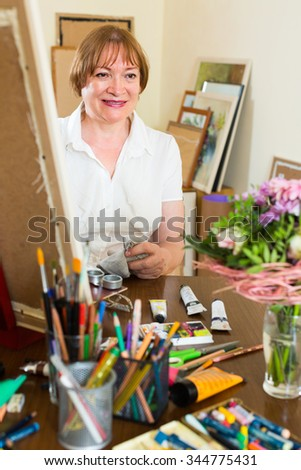 Happy smiling mature woman painting for fun with paints at home - stock photo