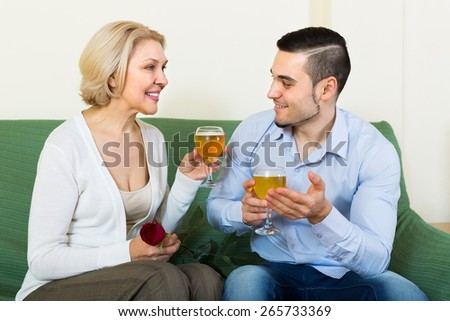 Happy smiling mature woman with young boyfriend having date with wine indoors