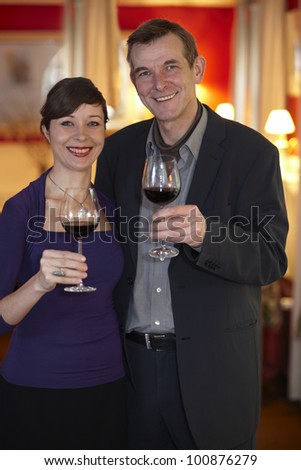 Happy smiling middle aged couple standing celebrating with glasses of red wine in plush red interior. - stock photo