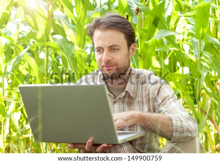 Happy smiling modern forty years old farmer checking his corn field and working on laptop computer while sunny summer day - stock photo