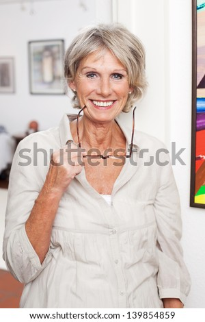 Happy smiling modern senior lady standing inside her house holding her reading glasses in her hand - stock photo