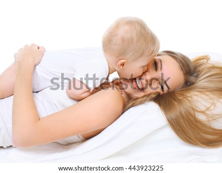 Happy smiling mother and baby playing together on bed  - stock photo