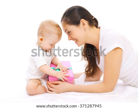Happy smiling mother and baby with gift box on a white background - stock photo