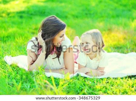 Happy smiling mother and child daughter lying together on grass in summer day