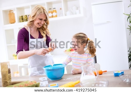 Happy smiling mother and daughter baking cookies