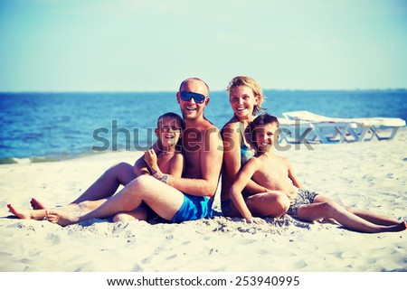 Happy smiling mother and father with two children sitting on the sunny beach.