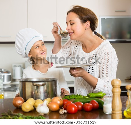 Happy smiling mother and her cheerful daughter preparing soup at kitchen