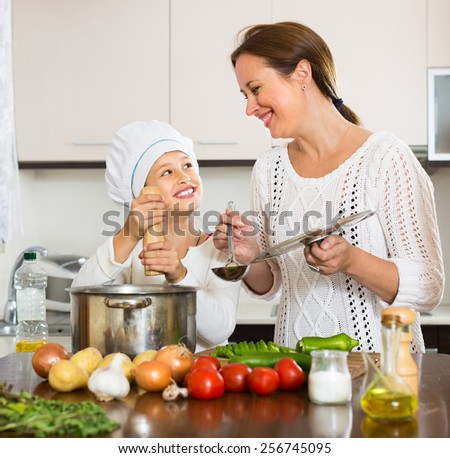 Happy smiling mother and her cheerful daughter preparing soup together at kitchen